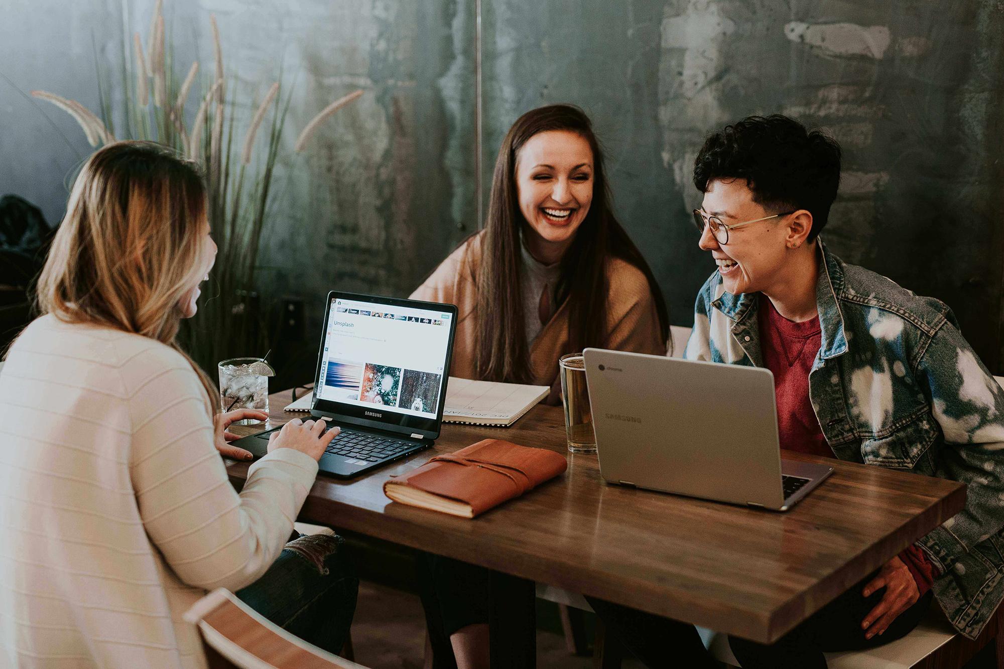 Drie lachende vrouwen achter hun laptops aan een tafel