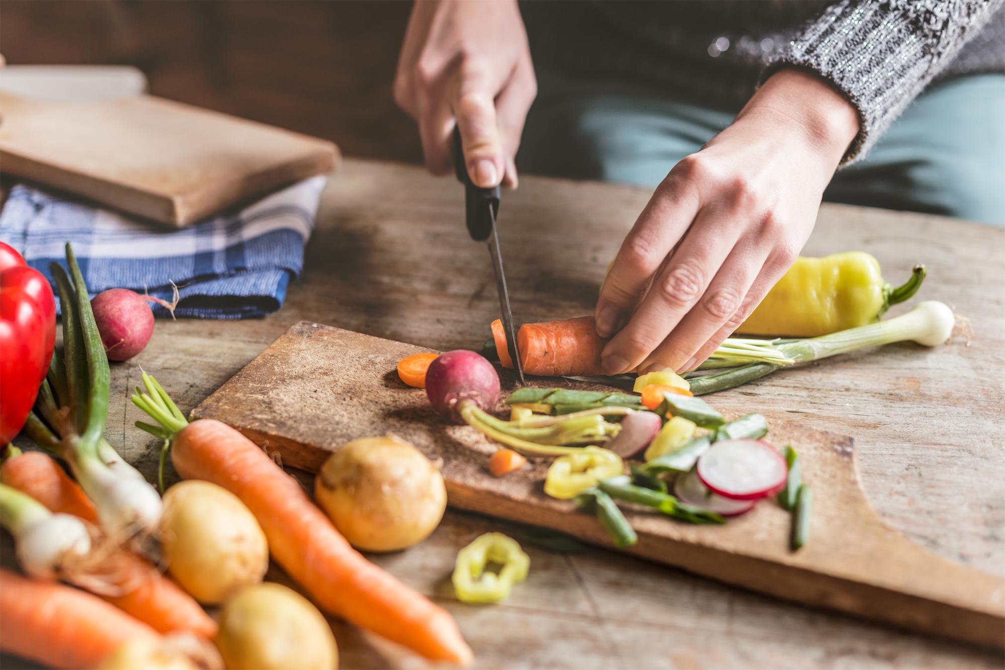 Handen die groenten snijden