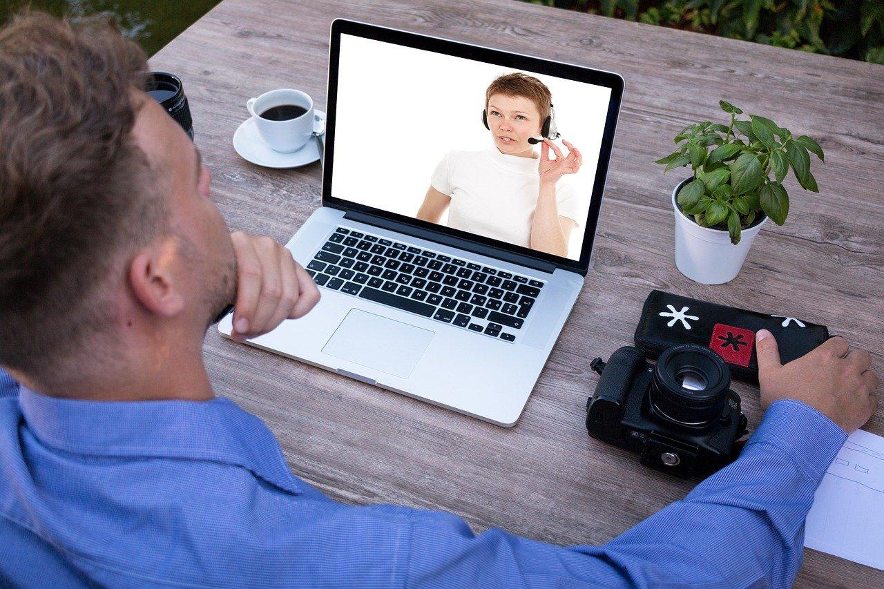 Man zit aan tafel en kijkt op zijn laptop.